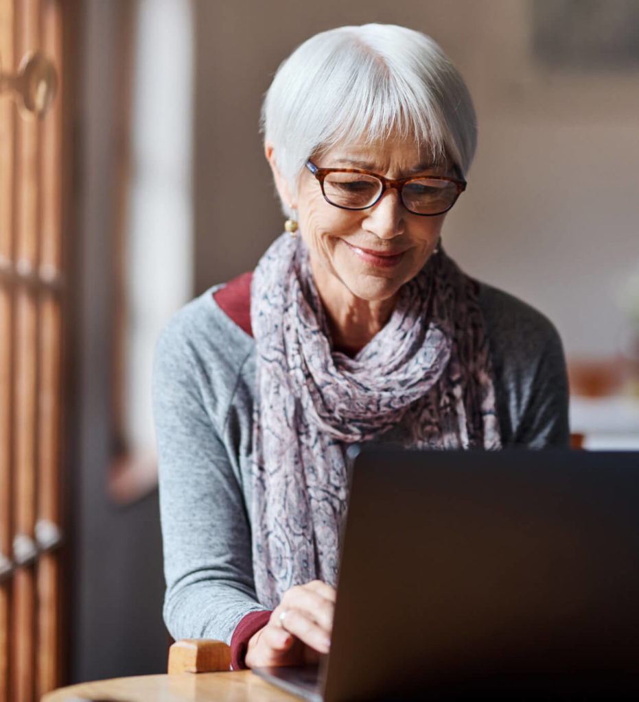 Woman sitting at computer using Hometown Health Clinic Telehealth