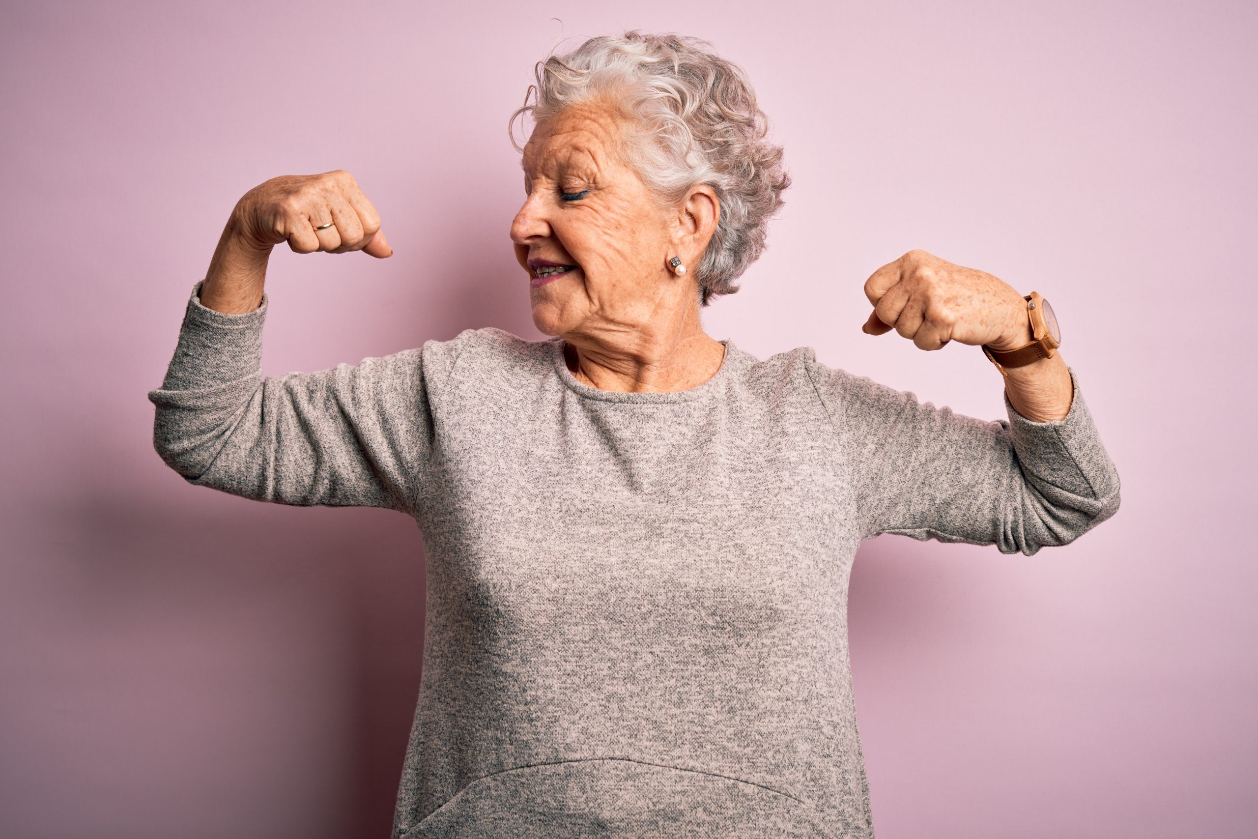 Senior beautiful woman wearing casual t-shirt standing over isolated pink background showing arms muscles smiling proud. Fitness concept.