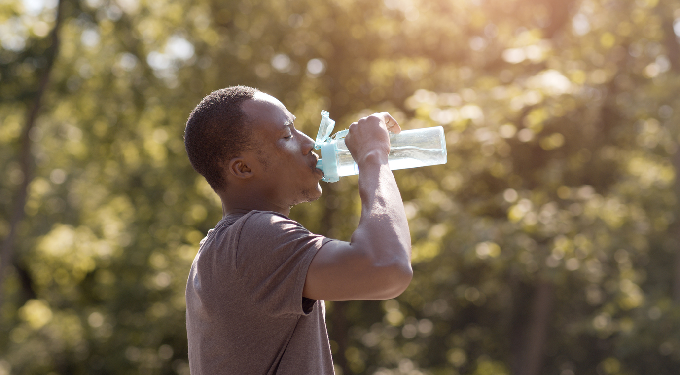 Overheated guy drinking water from bottle in park - Hometown Health Clinic