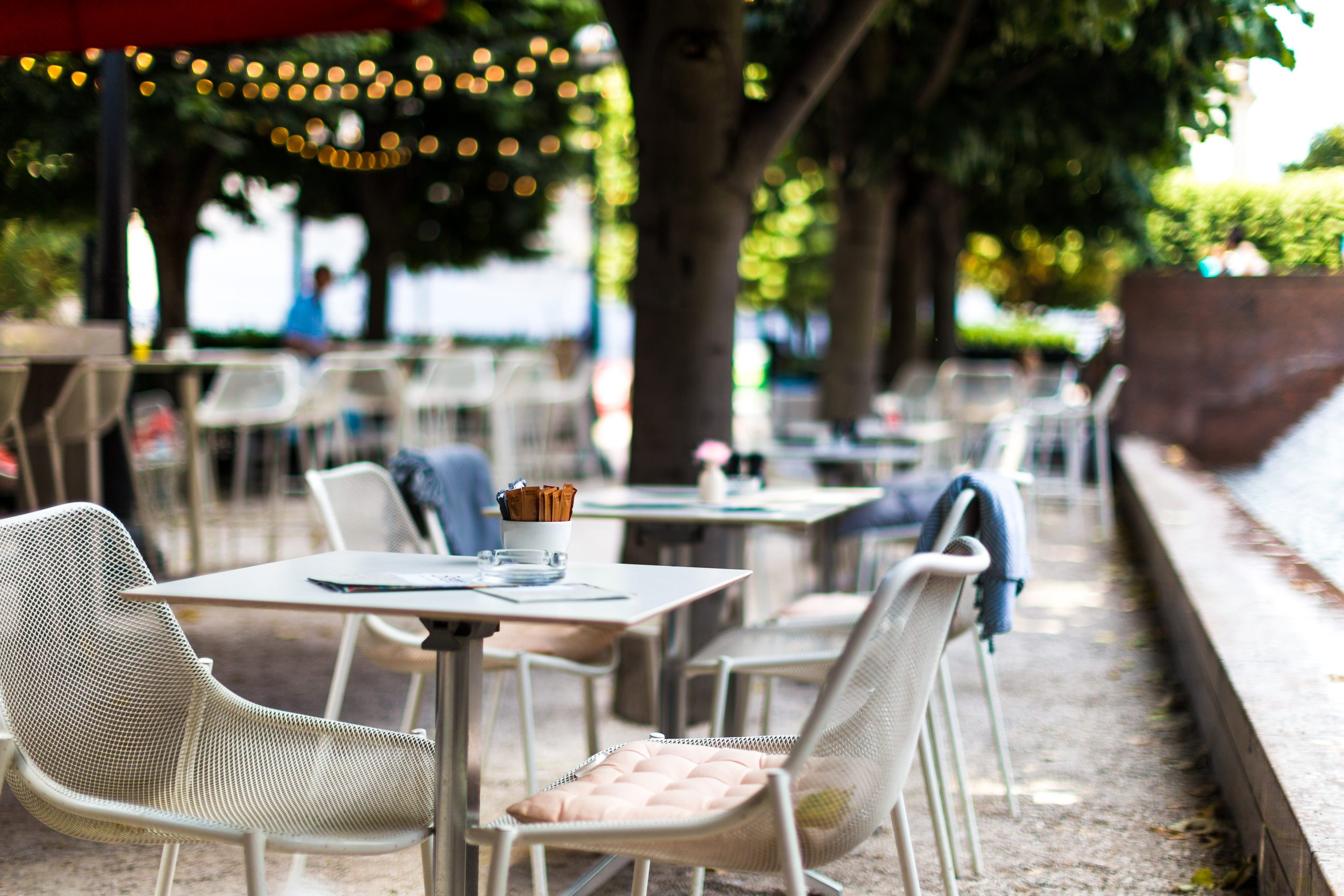 Color image depicting chairs and tables arranged at an outdoors cafe in central London, UK. It is a beautiful green space lined with trees and illuminated with fairy lights. There are bowls of sugar on the tables, but there are no people around. Room for copy space.